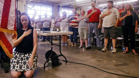 Selectwoman Melissa Schlag kneels for the Pledge of Allegiance during a Haddam, Conn., board of selectmen meeting on Monday, July 30, 2018 at the Haddam firehouse. Protestors and supporters gathered Monday night around a Haddam Town Meeting to address the recent controversy generated by Schlag's protest of the Pledge of Allegiance. Sarah Gordon/The Day/AP