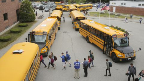 As classes let out, students walk to their respective buses, which will drive them home from Kennebunk High School in Maine in the United States.