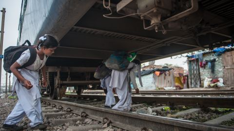 Children cross a stationed train during their school commute in Delhi, India.