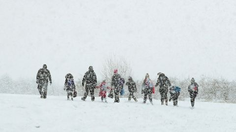 As heavy snow falls, parents walk their children to school in Ashford, a town in the county of Kent, England.