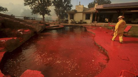 A firefighter walks around a swimming pool that had been sprayed by fire retardant near Lakeport.