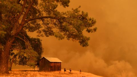 TOPSHOT - Firefighters watch as flames from the County Fire climb a hillside in Guinda, California, on July 1, 2018. - Californian authorities have issued red flag weather warnings and mandatory evacuation orders after a series of wildfires fanned by high winds and hot temperatures ripped through thousands of acres. The latest blaze, the County Fire sparked in Yolo County on June 30, had by July 1 afternoon spread across 22,000 acres (9,000 hectares) with zero percent containment, according to Cal Fire. (Photo by JOSH EDELSON / AFP)        (Photo credit should read JOSH EDELSON/AFP/Getty Images)
