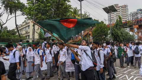 A Bangladeshi student wave Bangladesh's national flag as they block a road during a student protest in Dhaka on August 4, 2018, following the deaths of two college students in a road accident . - Parts of the Bangladeshi capital ground to a halt for the seventh day running on August 4, as thousands of students staged protests calling for improvements to road safety after two teenagers were killed by a speeding bus. (Photo by MUNIR UZ ZAMAN / AFP)        (Photo credit should read MUNIR UZ ZAMAN/AFP/Getty Images)