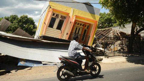 TOPSHOT - A man riding a motorcycle passes by a damaged house at Sira village in northern Lombok in West Nusa Tenggara province on August 7, 2018, two days after the area was struck by an earthquake. - The shallow 6.9-magnitude quake killed at least 98 people and destroyed thousands of buildings in Lombok on August 5, just days after another deadly tremor surged through the holiday island and killed 17. (Photo by SONNY TUMBELAKA / AFP)        (Photo credit should read SONNY TUMBELAKA/AFP/Getty Images)