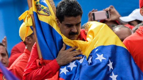"""TOPSHOT - Venezuelan President Nicolas Maduro holds a national flag during the closing of the campaign to elect a Constituent Assembly that would rewrite the constitution, in Caracas on July 27, 2017 on the second day of a 48-hour general strike called by the opposition. Venezuela's opposition called for a nationwide protest on Friday in outright defiance of a new government ban on demonstrations ahead of a controversial weekend election. """"The regime declared we can't demonstrate... We will respond with the TAKING OF VENEZUELA tomorrow,"""" the opposition coalition, the Democratic Unity Roundtable, said Thursday on its Twitter account.  / AFP PHOTO / Federico PARRA        (Photo credit should read FEDERICO PARRA/AFP/Getty Images)"""