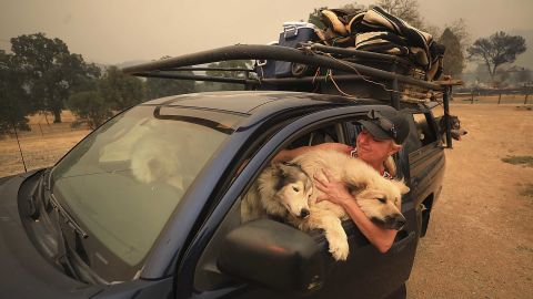 Crystal Easter comforts her dogs as they flee a wildfire in Spring Valley on Monday, August 6.