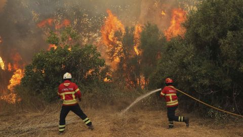 Firefighters try to extinguish a wildfire in Monchique, Portugal, on Tuesday, August 7.