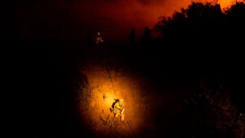 A firefighter makes his way down a hillside while battling the Mendocino Complex Fire on August 7.