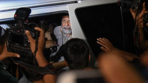 Activists and photographer Shahidul Alam looks out from a vehicle as he arrives for an appearance in a court in Dhaka on Monday.