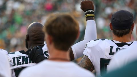 Malcolm Jenkins #27 of the Philadelphia Eagles raises his fist during the national anthem as Chris Long #56 puts his arm around him prior to a preseason game. Mitchell Leff/Getty Images