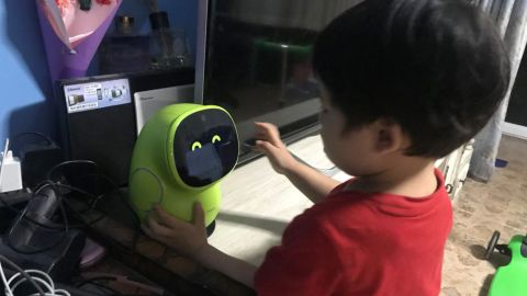 Three-year-old Seven Kong plays with the android, named BeanQ.