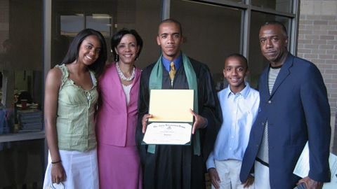 Clint Smith in cap and gown with  family at his high school graduation from The Awty International School in Houston.
