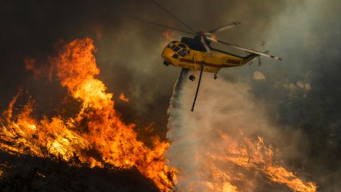 A helicopter drops water on flames in Lake Elsinore, California, on Friday, August 10.