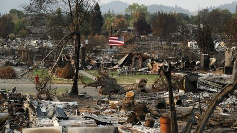 A flag flies at half-staff amid the rubble of homes burned in the Carr Fire, on Sunday, August 12.