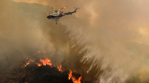 A helicopter drops water to a brush fire at the Holy Fire in Lake Elsinore, California, southeast of Los Angeles, on August 11, 2018. - The fire has burned 21,473 acres and was 29 percent contained as of 8:30 a.m. Saturday, according to the Cleveland National Forest. (Photo by RINGO CHIU / AFP)        (Photo credit should read RINGO CHIU/AFP/Getty Images)