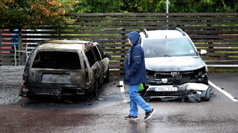 A person walks past burned cars parked at Frölunda Square in Gothenburg, Sweden, on Tuesday.