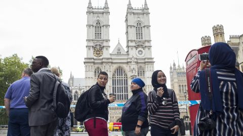 Siti Atikah Binti ABD Razak, 19, second from right, is photographed by her sister, Siti Nadhirah Binti ABD Razak, 21 (far right with back turned) outside Westminster Abbey, which was not accessible due to the ongoing police investigation.