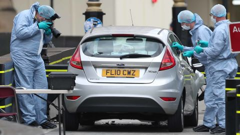Police forensics officers work around a silver Ford Fiesta car that was driven into a barrier at the Houses of Parliament in central London on August 14.