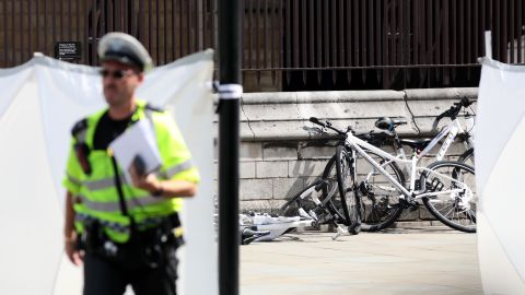 Police officers stand guard near bicycles believed to have been damaged in the crash