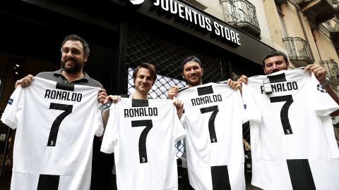 Juve supporters show off their Cristiano Ronaldo jerseys in front of the club's shop in Turin after the Serie A team signed the Portuguese star.