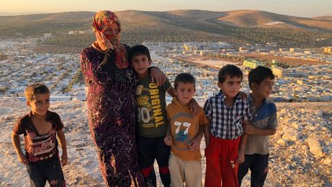 """Vaciha Turki Al Omar, 30, has been in Idlib for seven months. She on the hill overlooking the sprawling refugee camp with her kids. """"We can try to fight but the kids are our weakness so we must run away,"""" she says."""