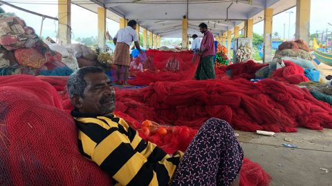 A volunteer fishermen rests on his nets in an evacuation operation in Kollam, India.
