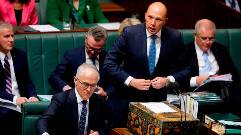 Australia's then-Minister for Home Affairs Peter Dutton (2nd R) speaks at Parliament as Australian Prime Minister Malcolm Turnbull (bottom L) looks at his notes in Canberra on August 20.