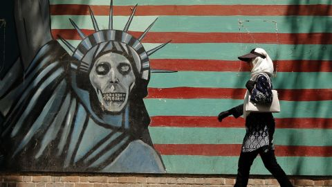 """An Iranian woman walks past a mural depicting the Statue of Liberty with a dead face, painted on the wall of the former US embassy in the capital Tehran on August 7, 2018 - US President Donald Trump warned countries against doing business with Iran today as he hailed the """"most biting sanctions ever imposed"""", triggering a mix of anger, fear and defiance in Tehran. (Photo by ATTA KENARE / AFP)        (Photo credit should read ATTA KENARE/AFP/Getty Images)"""