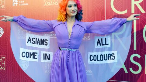 """Burlesque performer Sukki Singapora poses for photographers as she arrives for the red carpet screening of """"Crazy Rich Asians."""""""