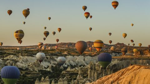 <strong>Cappadocia, Turkey: </strong>Hot-air balloons rise into the sky at sunset, allowing tourists stunning views of cone-shaped rock formations and rippled ravines.