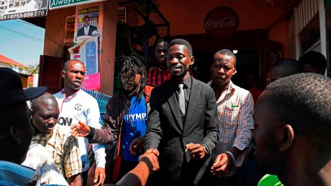 """Musician turned politician, Robert Ssentamu Kyagulanyi commonly known as """"Bobi wine"""" (C) shakes hands with his supporters in a suburb of Kampala on June 30, 2017."""