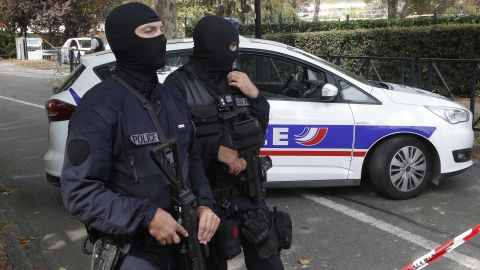 French hooded police officers cordon off the area after a knife attack Thursday, Aug. 23, 2018 in Trappes, west of Paris. A man flagged by French authorities as a suspected radical killed his mother and sister and seriously injured another woman in a knife attack Thursday that was quickly claimed by the Islamic State group. (AP Photo/Michel Euler)