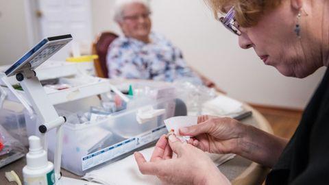 Janie York cleans Elaine Martin's hearing aids.