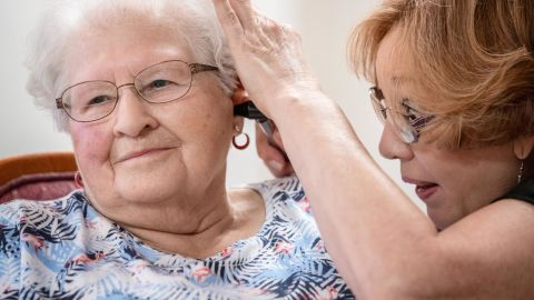 Janie York examines Elaine Martin's ear at the SilverRidge Assisted Living facility in Gretna, Nebraska.