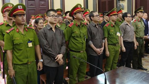 Members of California-based Provisional National Government of Vietnam stand with policemen during a trial in Ho Chi Minh city on August 22, 2018.
