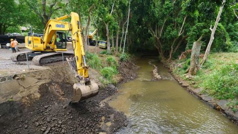 Workers clean debris from a stream near Honolulu, trying to get ahead of water from the hurricane.