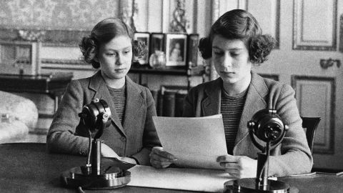A 14-year-old Elizabeth, right, sits next to her sister for a radio broadcast on October 13, 1940. On the broadcast, her first, she said that England's children were full of cheerfulness and courage.