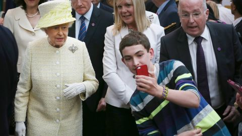 A boy in Belfast, Northern Ireland, takes a selfie in front of the Queen in June 2014.