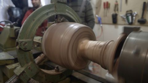 Once the wood is sufficiently dry, structural detail is carved into the drum's exterior surface -- a painstaking process carried out with a hand-powered lathe.