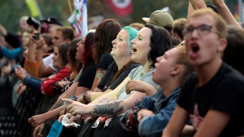 Concert-goers in the front row cheer on performers.