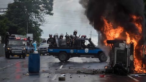 Heavily armed police officers sit on a pick-up and stand next to a burning police car in Managua on September 2, 2018.
