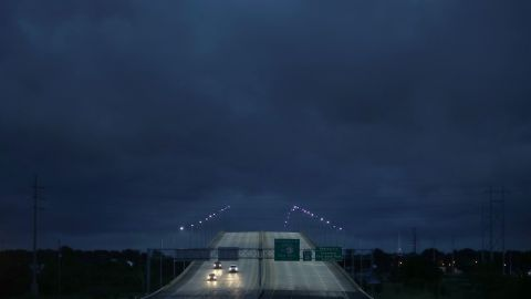 Vehicles pass over a US Route 90 bridge as Tropical Storm Gordon darkened the skies in Pascagoula, Mississippi, on September 4.
