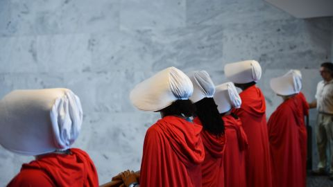 """Women dressed as characters from the novel-turned-TV series """"The Handmaid's Tale"""" line up  before Supreme Court nominee Brett Kavanaugh starts the first day of his confirmation hearing in front of the US Senate on Capitol Hill in Washington DC, on September 4, 2018. - President Donald Trump's newest Supreme Court nominee Brett Kavanaugh is expected to face punishing questioning from Democrats this week over his endorsement of presidential immunity and his opposition to abortion. Some two dozen witnesses are lined up to argue for and against confirming Kavanaugh, who could swing the nine-member high court decidedly in conservatives' favor for years to come. Democrats have mobilized heavily to prevent his approval. (Photo by Brendan Smialowski / AFP)        (Photo credit should read BRENDAN SMIALOWSKI/AFP/Getty Images)"""