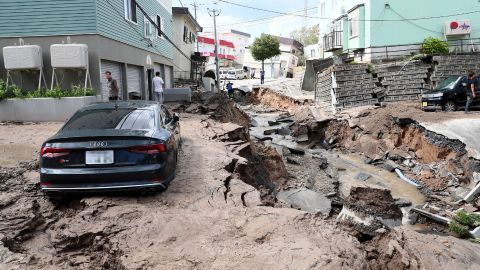A car is seen stuck on a road damaged by an earthquake in Sapporo, Japan, on September 6, 2018.