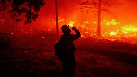 A firefighter drinks water as flames spread Thursday in Pollard Flat.