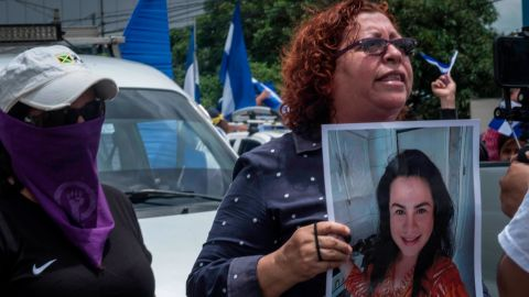 A mother holds up a photo of her daughter she says was imprisoned for protesting.
