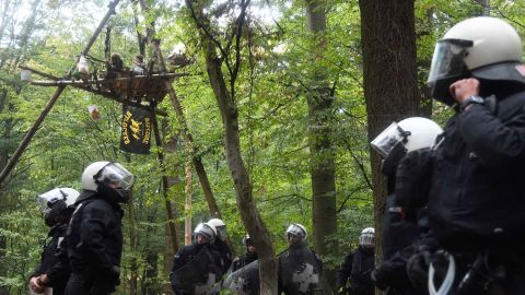 Activists sit on a platform in Hambach Forest as police officers arrive to begin clearance operations.