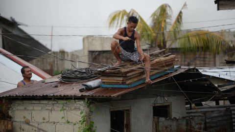 Residents secure the roof of their house as Typhoon Mangkhut approaches the city of Tuguegarao, Cagayan province, north of Manila on September 14, 2018. - Preparations were in high gear in the Philippines on September 14 with Super Typhoon Mangkhut set to make a direct hit in less than 24 hours, packing winds up to 255 kilometres per hour and drenching rains. (Photo by TED ALJIBE / AFP)        (Photo credit should read TED ALJIBE/AFP/Getty Images)
