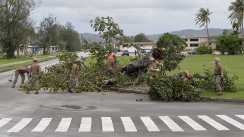"""Sailors remove debris on a US naval base in Guam on Tuesday, September 11, after the <a href=""""http://www.cnn.com/2018/09/12/asia/super-typhoon-mangkhut-ompong-wxc-intl/index.html"""">typhoon swept through the island territory</a>, causing flooding and power outages."""