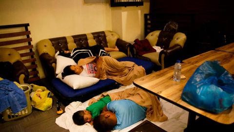 Guests sleep inside a hotel restaurant after strong winds damaged the roof of their room in Tuguegarao City on September 15.